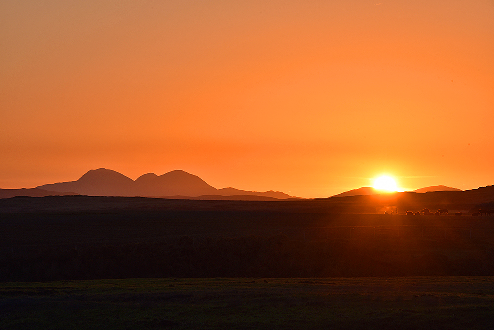 Picture of a colourful sunrise over a hilly landscape, some higher mountains on the left
