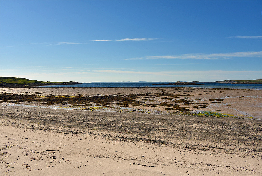 Picture of a view from a beach out of a sea loch towards another island
