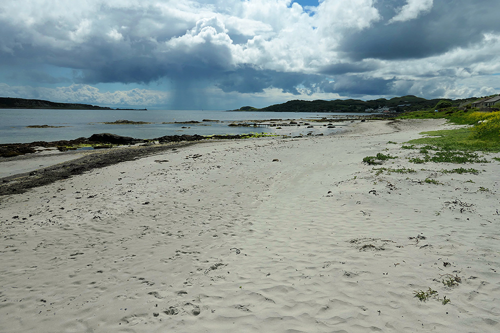 Picture of a small beach in a coastal village, a heavy rain shower in the distance
