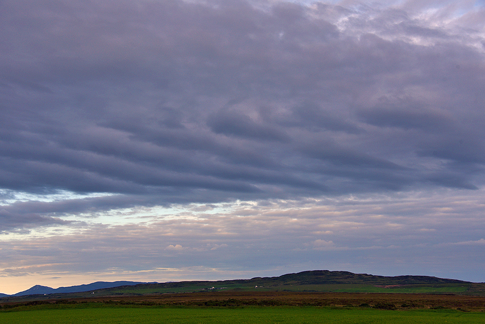 Picture of an interesting cloud formation above a hilly island landscape