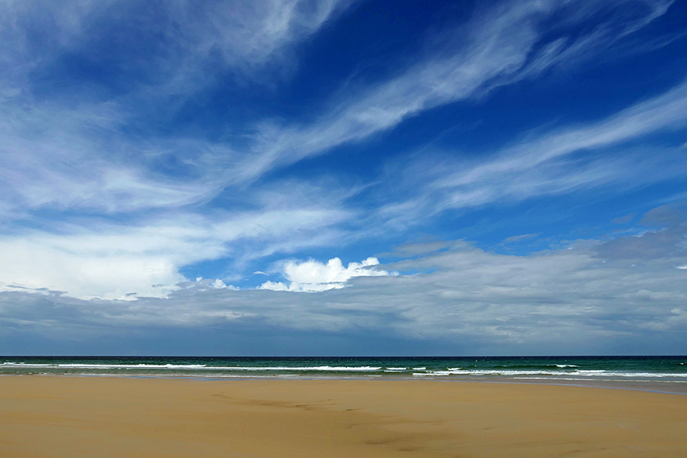 Picture of a variety of clouds over a beach looking out to the Atlantic