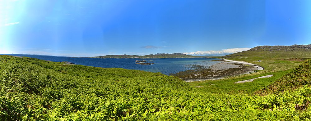 Panoramic picture of the entrance to a sea loch on a sunny afternoon