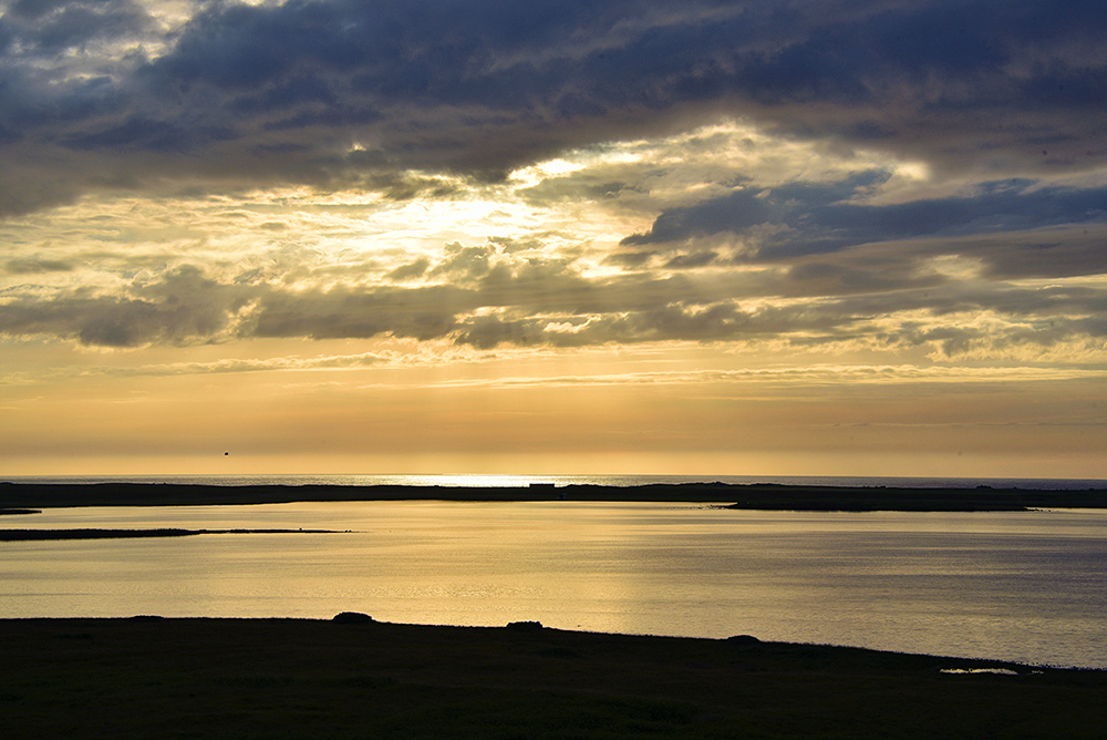 Picture of dramatic summer evening sky over a freshwater loch and an Atlantic coast line