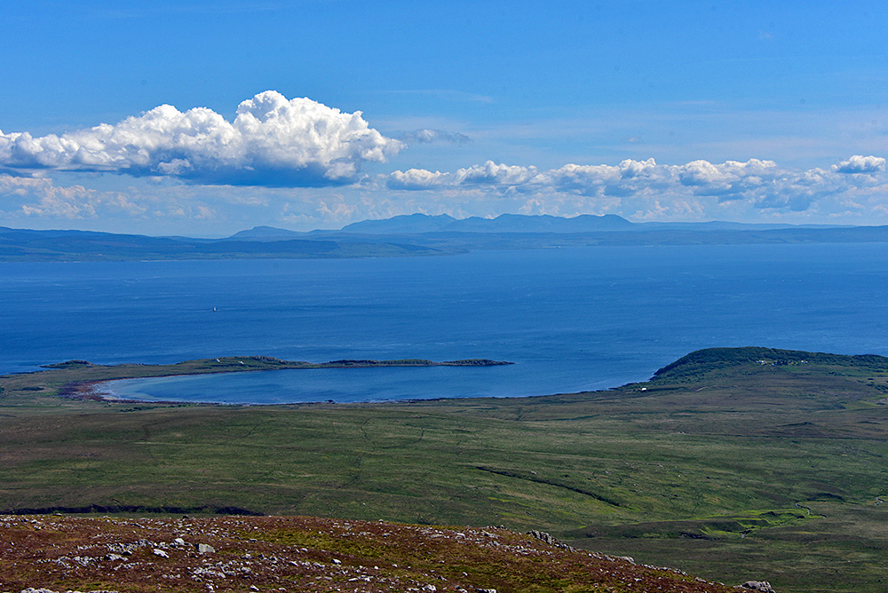 Picture of a view from a hill over a bay, a sound and the mainland with mountains in the distance
