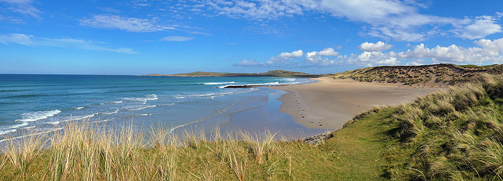 Panoramic picture of a bay with a sandy beach and dunes