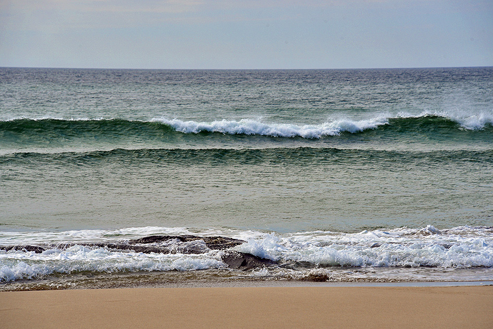 Picture of two waves rising and breaking as they approach a beach, also some small waves rolling out on the beach