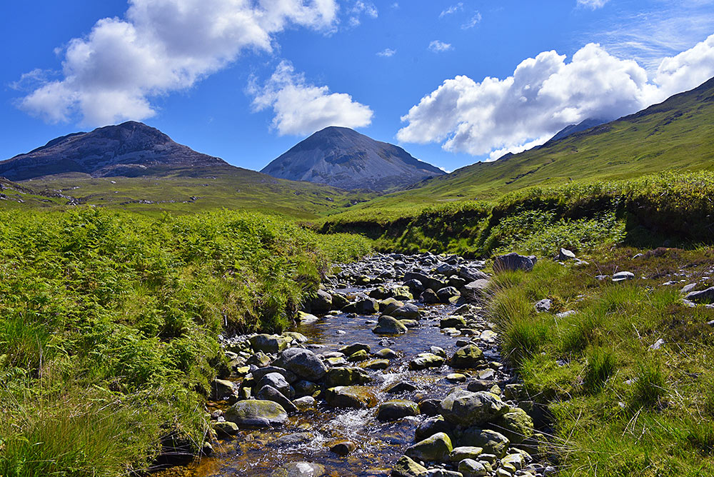 Picture of a small river flowing through a glen (valley) below two mountains