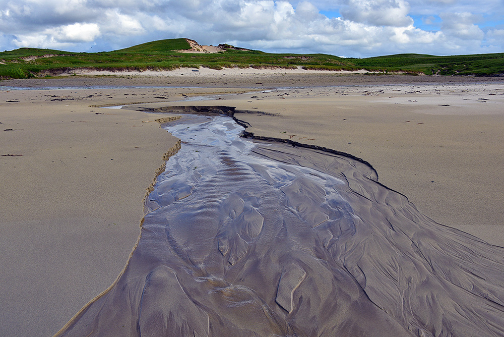 Picture of a small stream running across a beach, dunes in the background