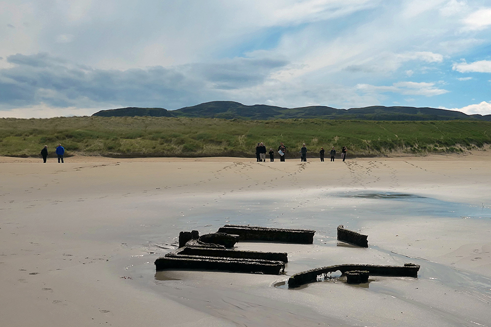 Picture of a wreck on a beach, several people behind it. Dunes and crags in the background