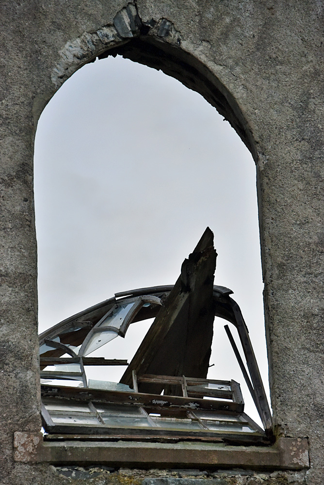 Picture of a fallen broken window at a ruined old church