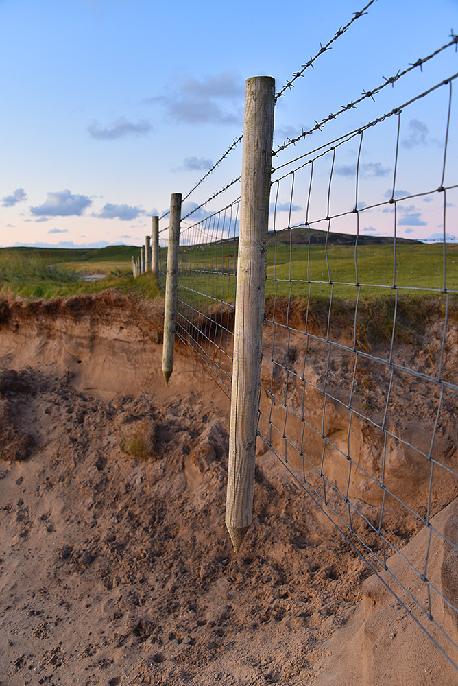 Picture of a stretch of fence floating (hanging) in the air, where the ground below it has eroded away