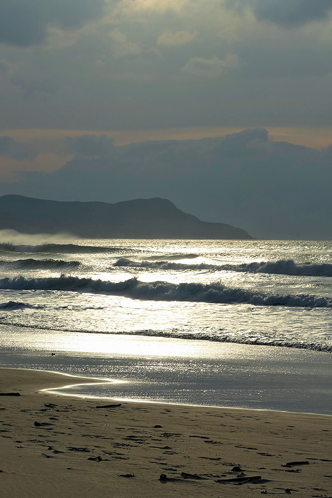 Picture of a bay seen from a beach bathed in beautiful golden hazy sunshine