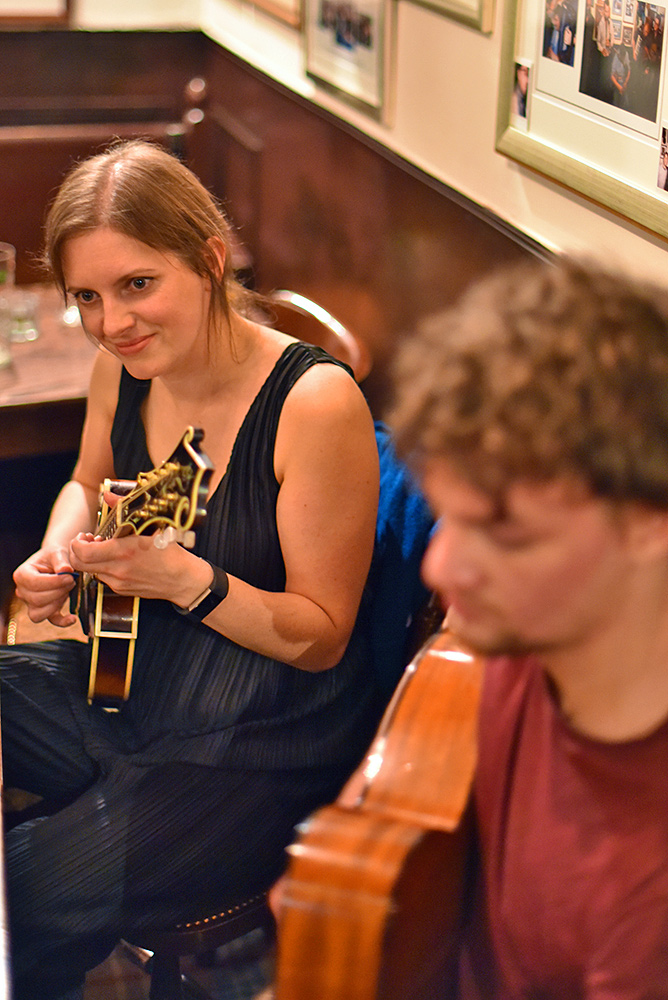 Picture of a female mandolin player in a bar, a blurry guitarist in the foreground