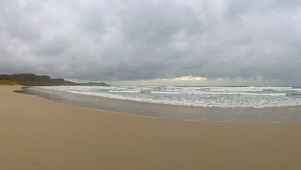 Panoramic picture of a big cloudy sky over a bay with a sandy beach