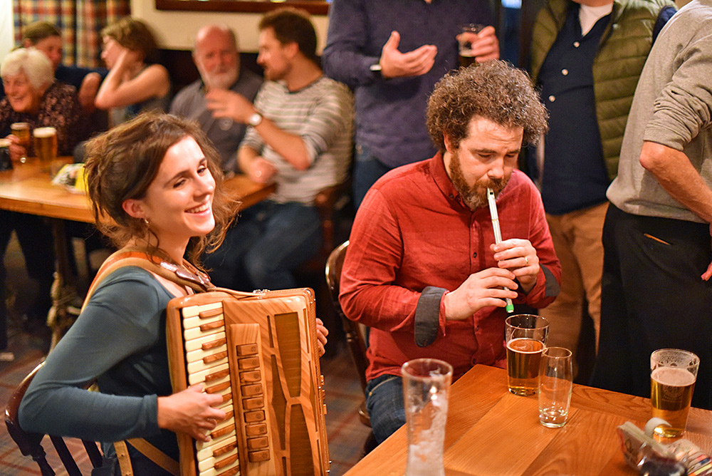 Picture of two musicians performing at a table in a bar
