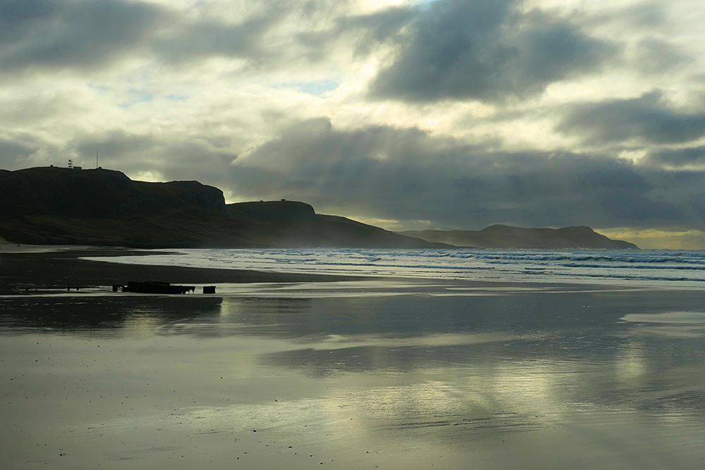 Picture of a bay with a sandy beach with some dark clouds broken up with some sunshine