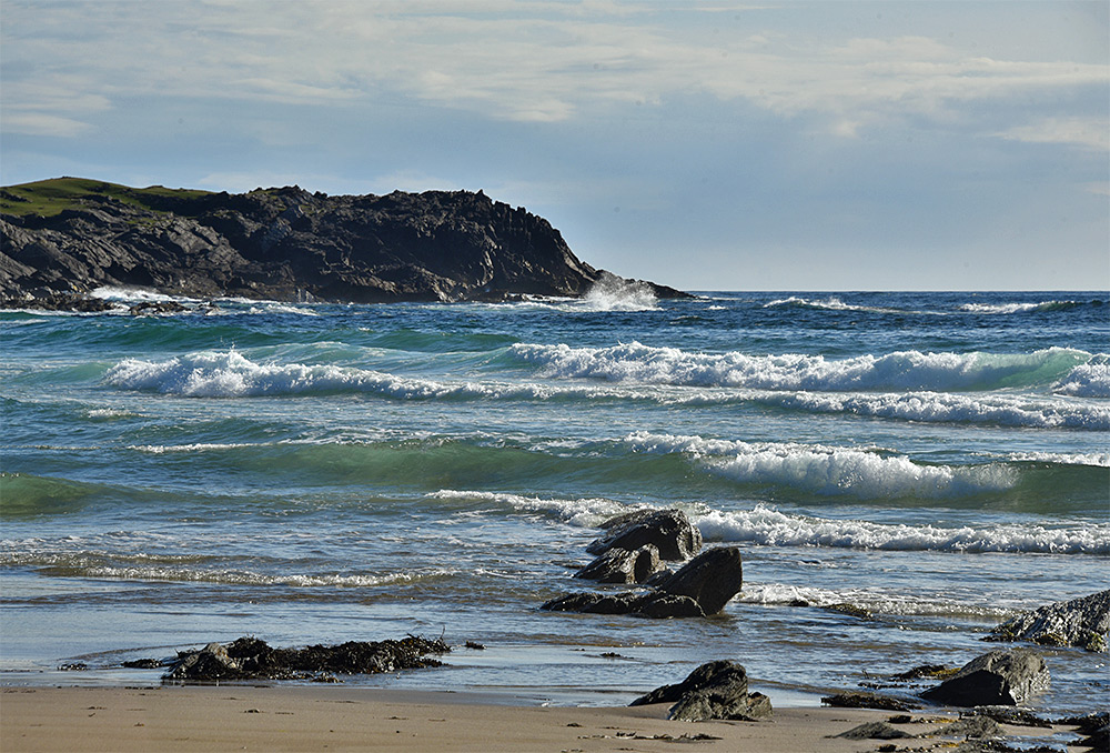 Picture of waves, beach and rocks in a bay
