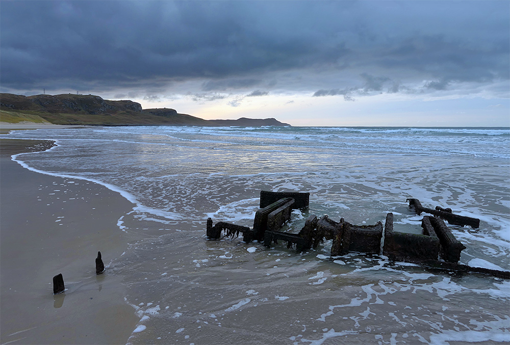 Picture of waves swirling around an old wreck on a sandy beach