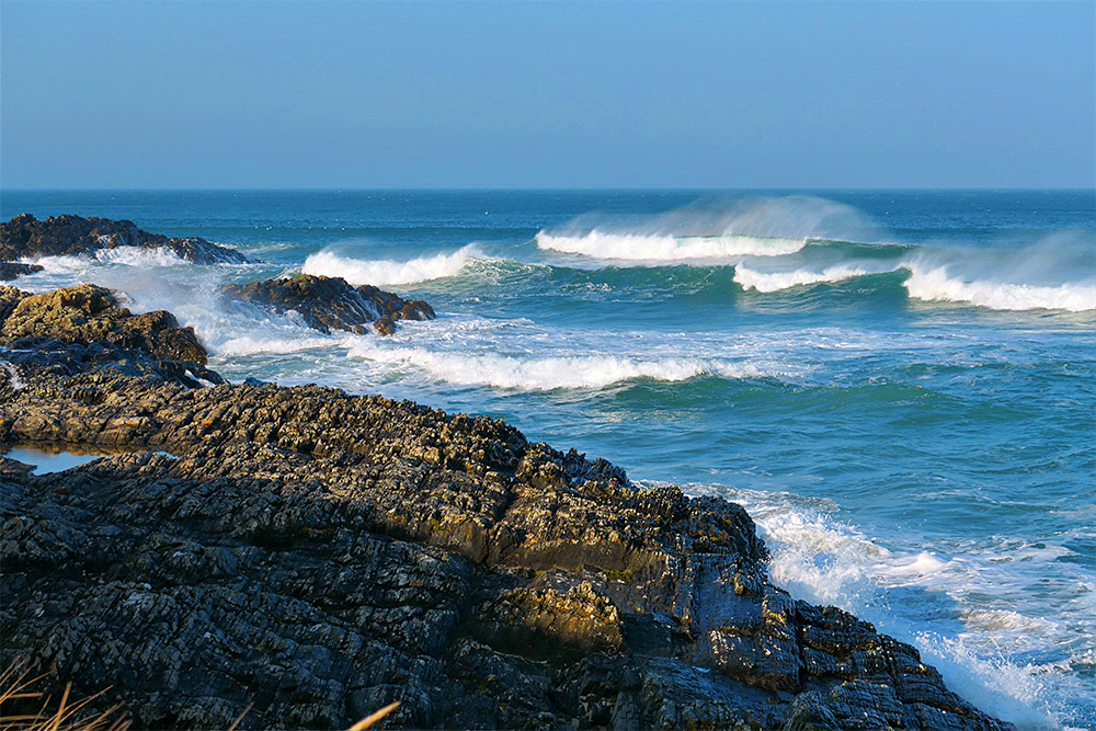 Picture of waves breaking in front of some steep rocks