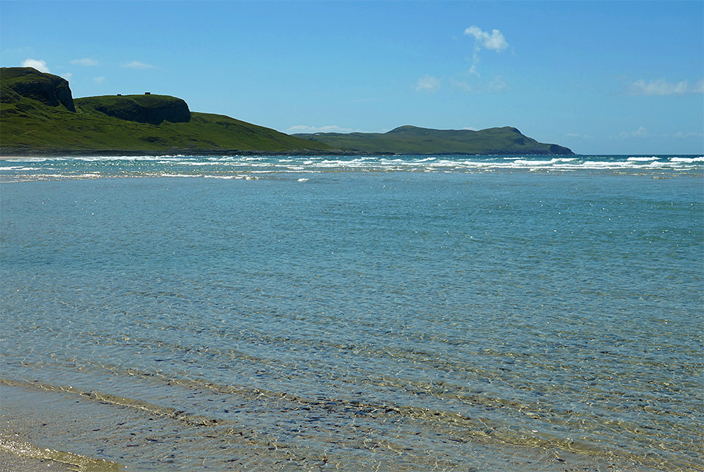Picture of shallow water on a beach, green hills in the background