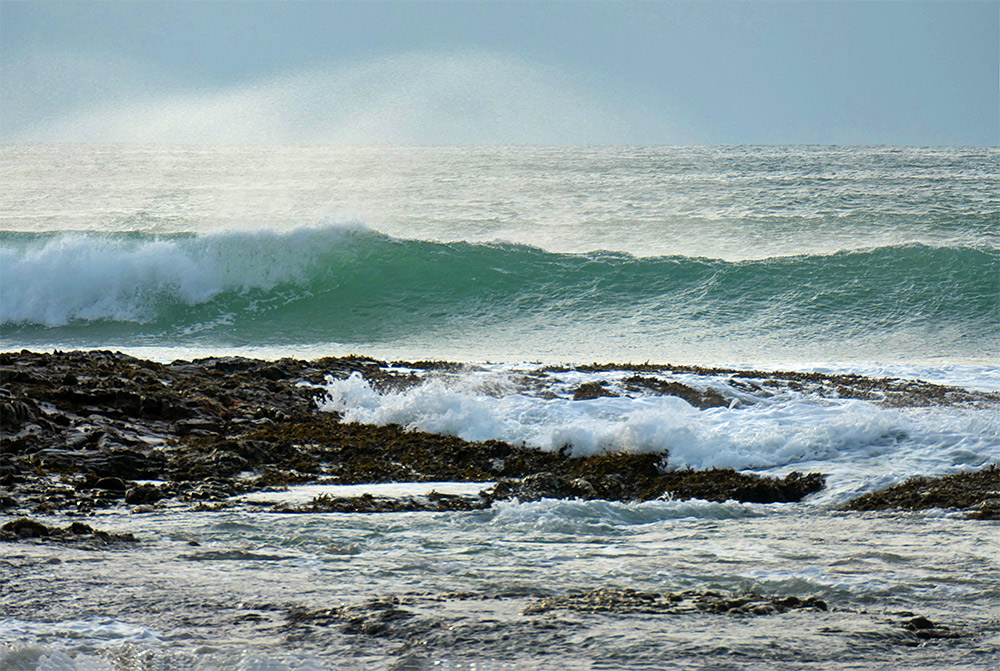 Picture of waves breaking and swirling at a rocky outcrop on a beach