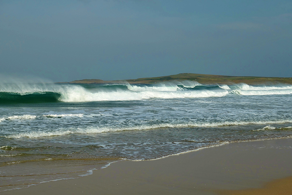 Picture of several breaking waves as they roll on to a beach, spray being blown back by the wind
