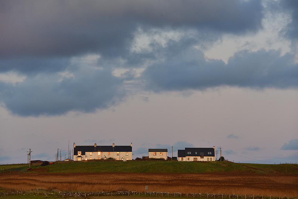Picture of a row of cottages in the sunshine during sunset, dark clouds overhead