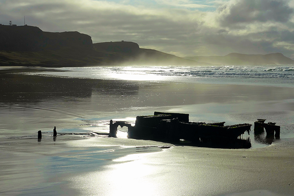 Picture of a wreck in a beach on a moody misty and cloudy but also sunny November morning