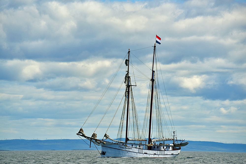 Picture of the SV Flying Dutchman motoring along a sound between an island and the mainland
