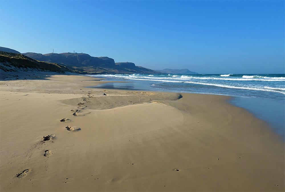 Picture of a sandy beach with footprints on a sunny April morning