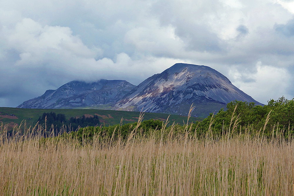 Picture of two scree covered mountains from behind a coastal wetland