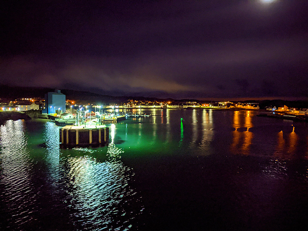 Picture of a small island harbour in a bay at night