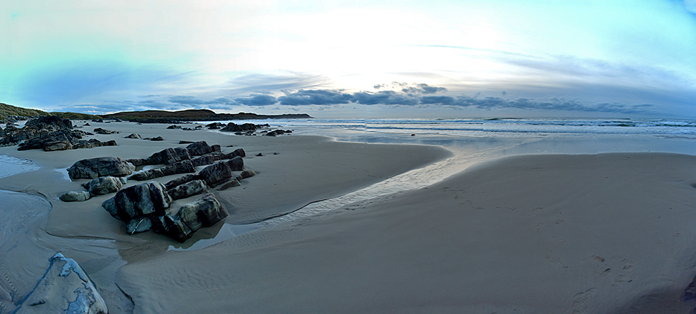 Panoramic picture of a bay with a sandy beach interspersed with rocks