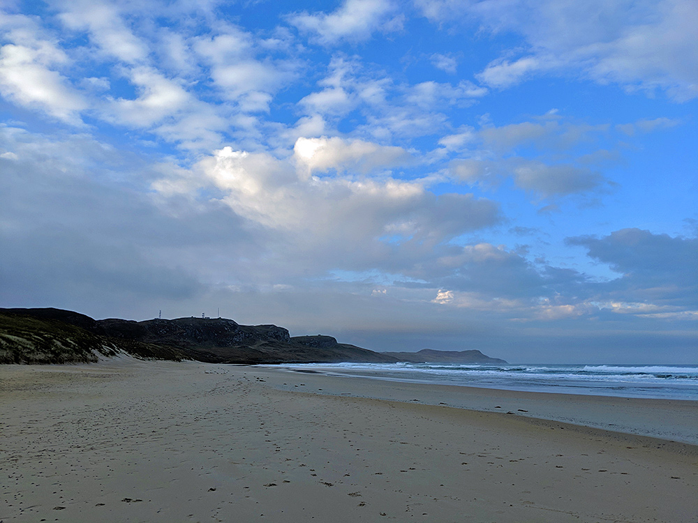 Picture of a beach in a bay with crags in the distance, sun and blue sky breaking through clouds