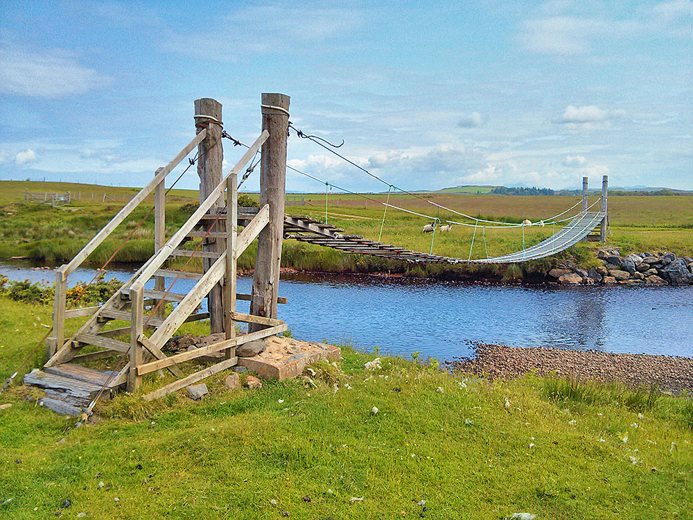Picture of a wooden rope bridge over a small river