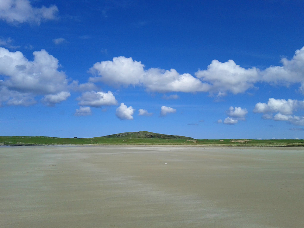 Picture of a wide sandy beach with some small white clouds above