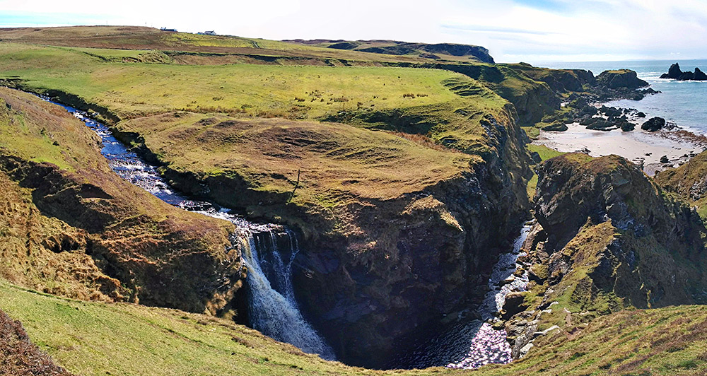 Panoramic picture of a burn with a waterfall near a coast with a beach