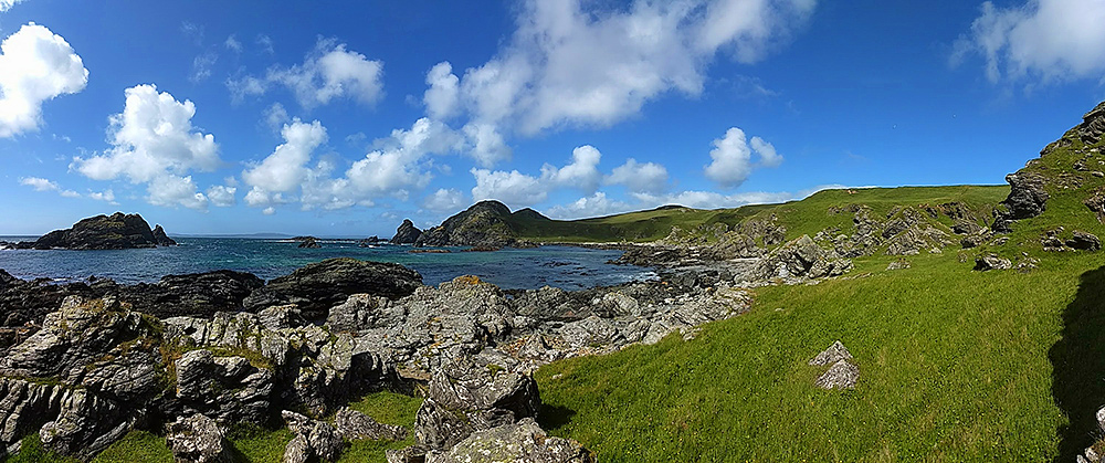Panoramic picture of a bay with a rocky shore and grassy hills