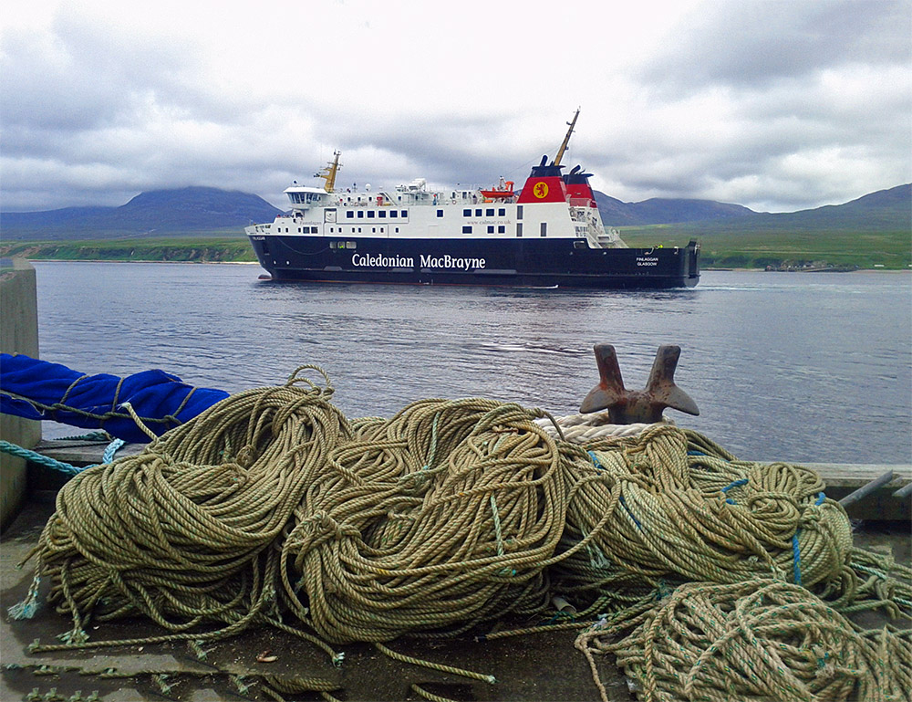 Picture of a modern ferry in a sound between two islands, lots of ropes on a pier in the foreground