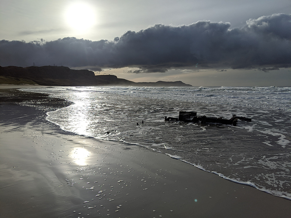 Picture of a beach with a wreck, the low November sun above a bank of clouds reflecting on the water and wet beach