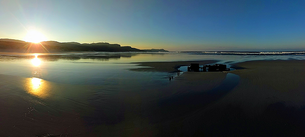 Panoramic picture of a beach with a wreck at sunrise in November