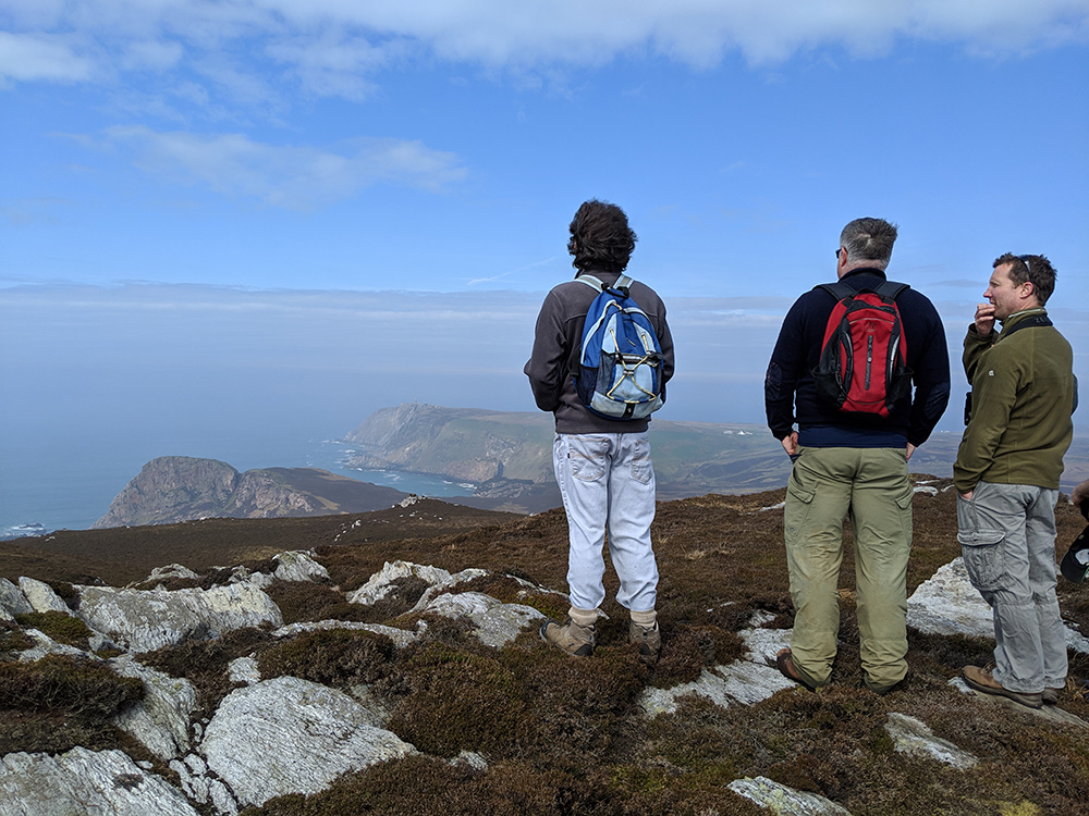 Picture of three walkers on a hill looking out over a hazy landscape and bay
