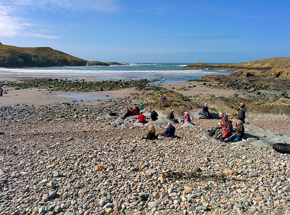 Picture of a group of walkers having lunch on a pebble beach