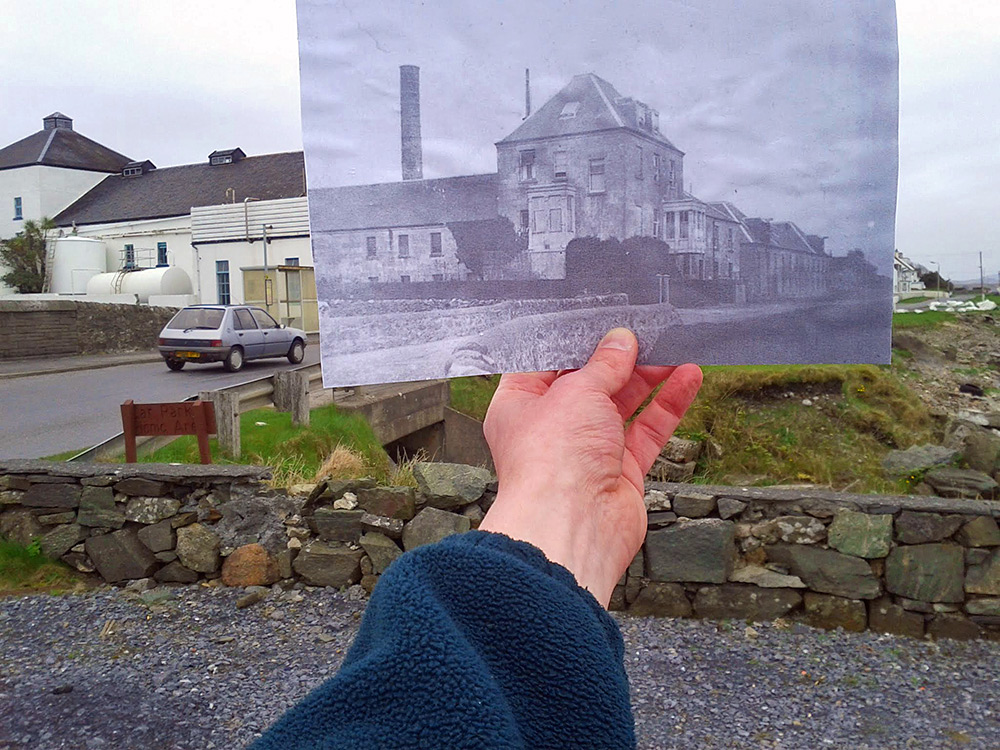 Picture of an old black and white picture of a distillery in a modern picture