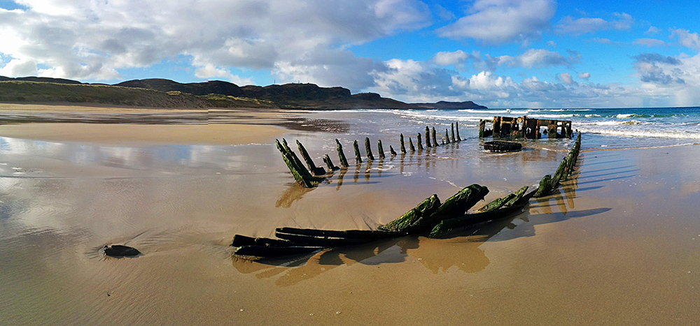 Panoramic picture of an old wreck in the sand of a beach on a bright June day