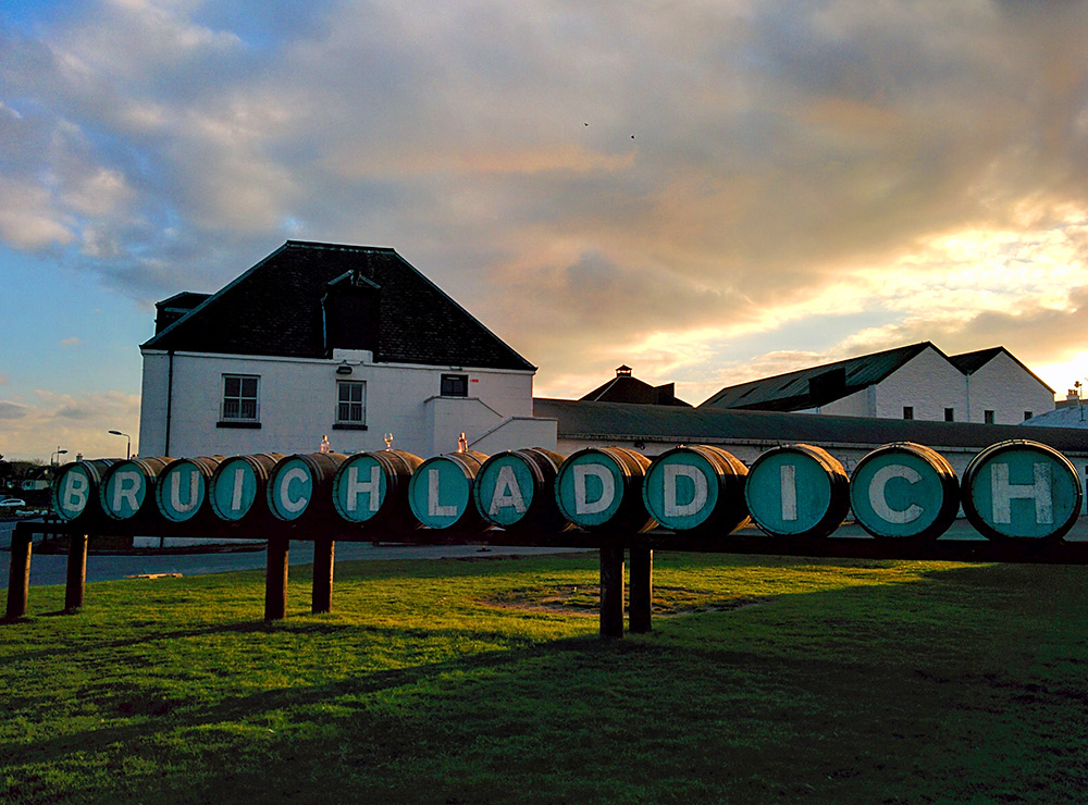 Picture of bottles and a glass on the Bruichladdich casks sign at the distillery on an April evening