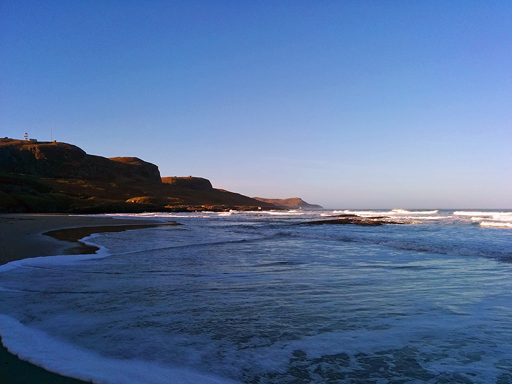 Picture of waves running over a beach in the shade of dunes and crags on a sunny morning