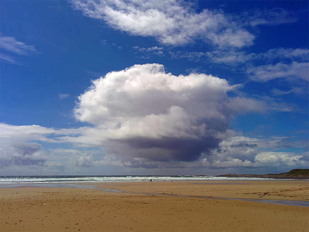 Picture of a huge dramatic cloud above two walkers on a beach