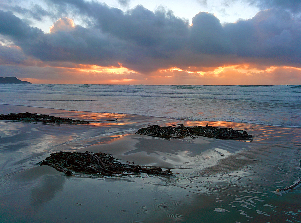 Picture of some dramatic colourful November afternoon light behind clouds in a bay with a beach