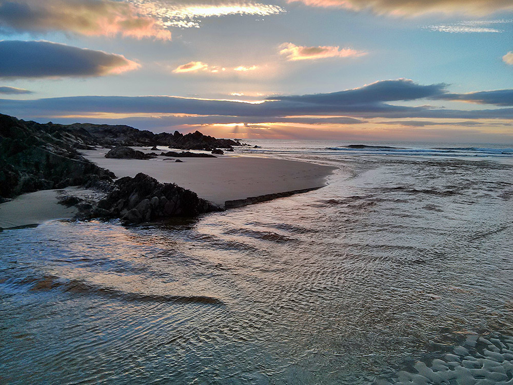 Picture of a dramatic sunset behind clouds, seen at a small river flowing over a sandy beach